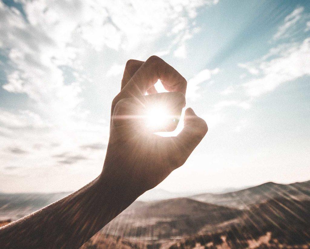 太陽を指で捉えてるかのような写真