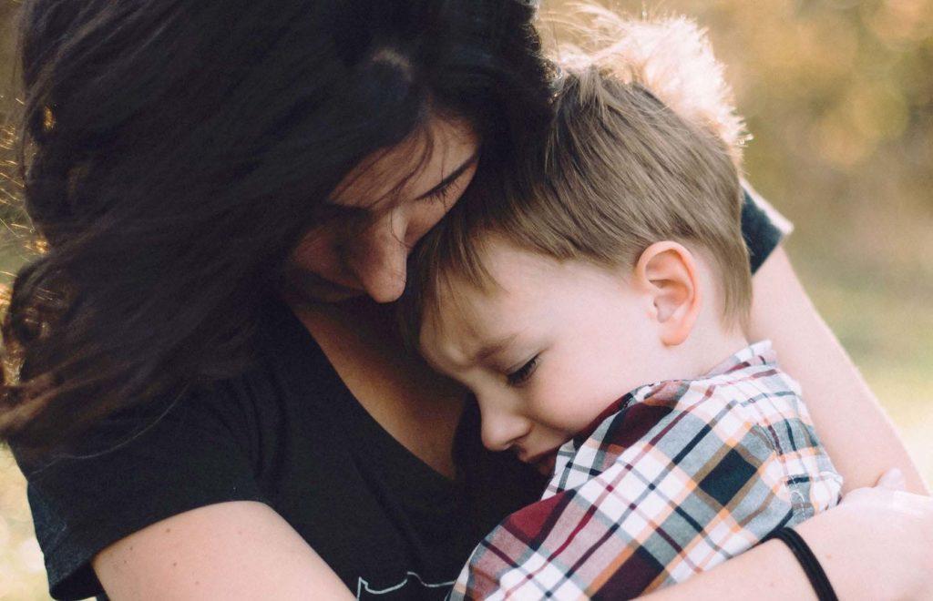 泣いてる子供を抱っこするママの写真