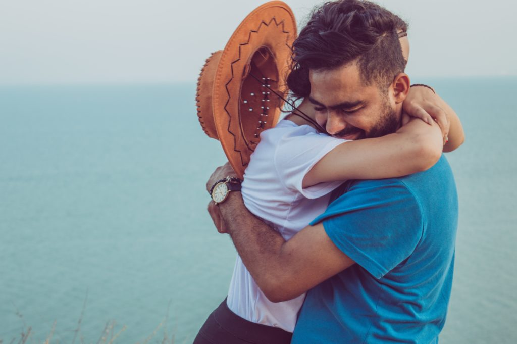 海辺で駆け寄って抱きつくカップルの写真