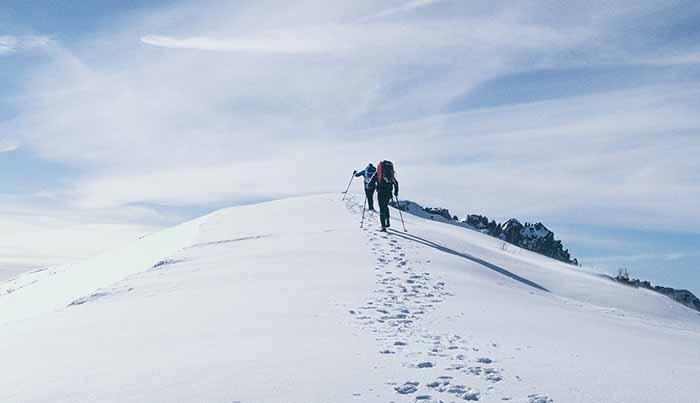 立ちはだかる山を登る人