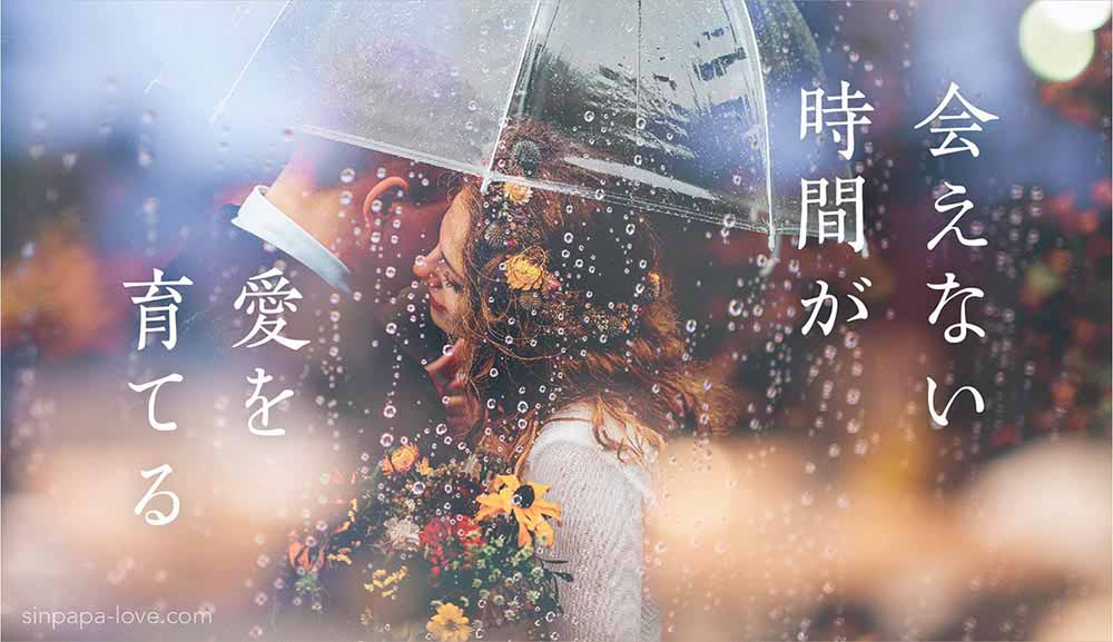 「会えない時間が愛を育てる」の文字と、雨の中一つの傘の下でハグするカップルの写真