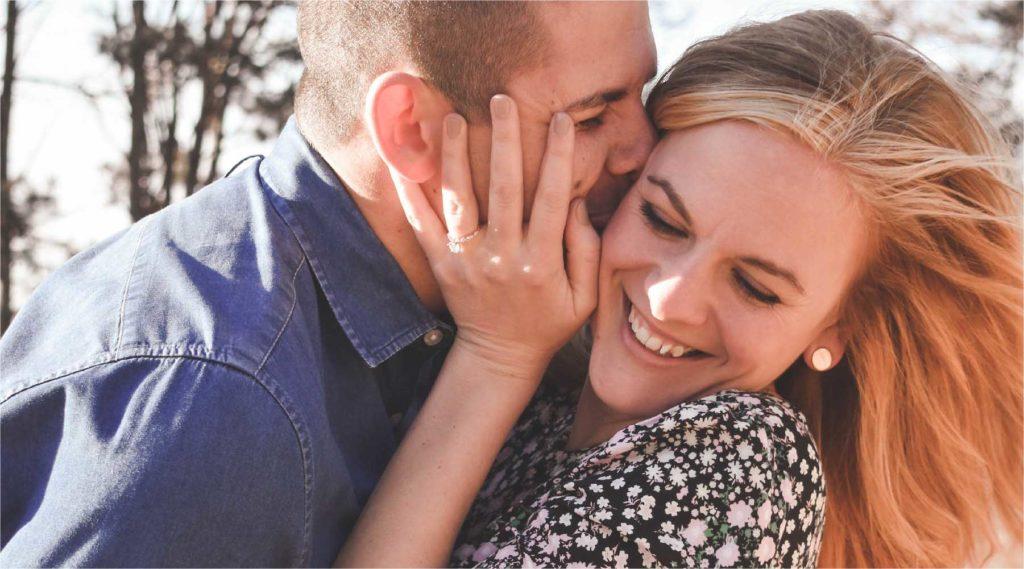 彼女に抱きついてキスをする幸せそうなカップルの写真