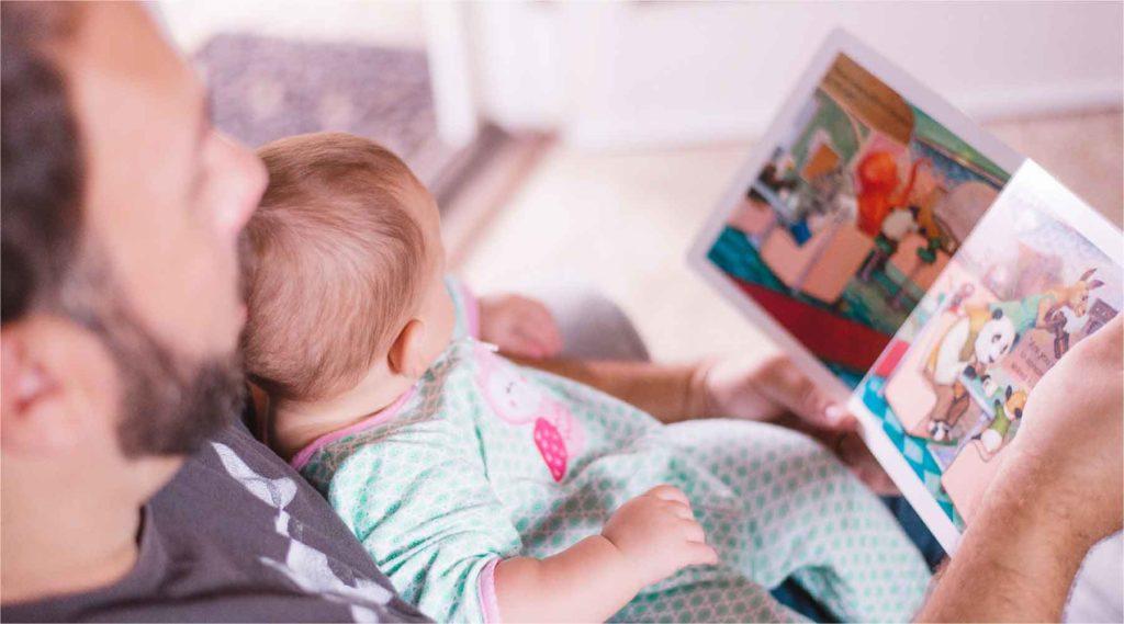 赤ちゃんを抱っこして絵本を読んで上げているパパの写真
