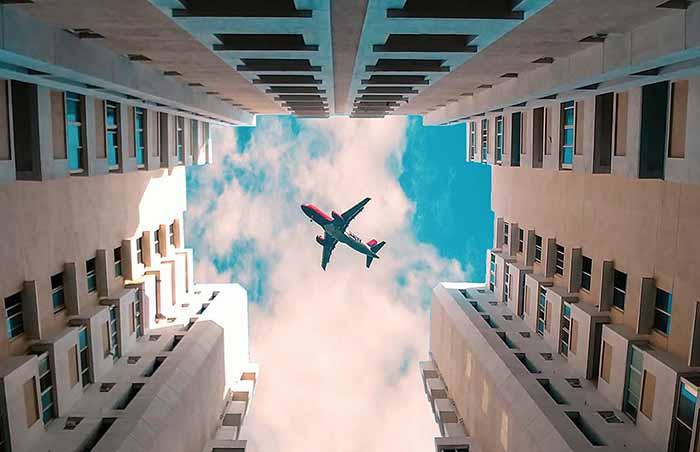 高層ビルの隙間に見える空に飛んでいる飛行機の写真