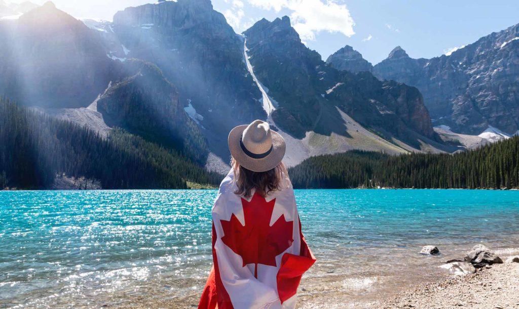 カナダの国旗をマントにし、大自然を見つめる人の後ろ姿