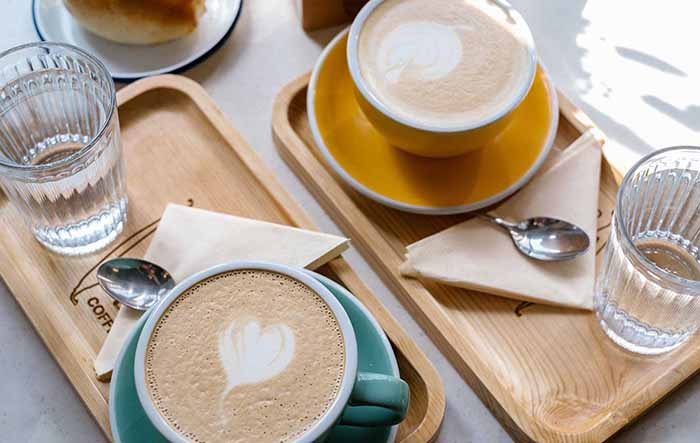 明るい日差しの中、黄色とブルーグリーンのコーヒーカップが並ぶ写真