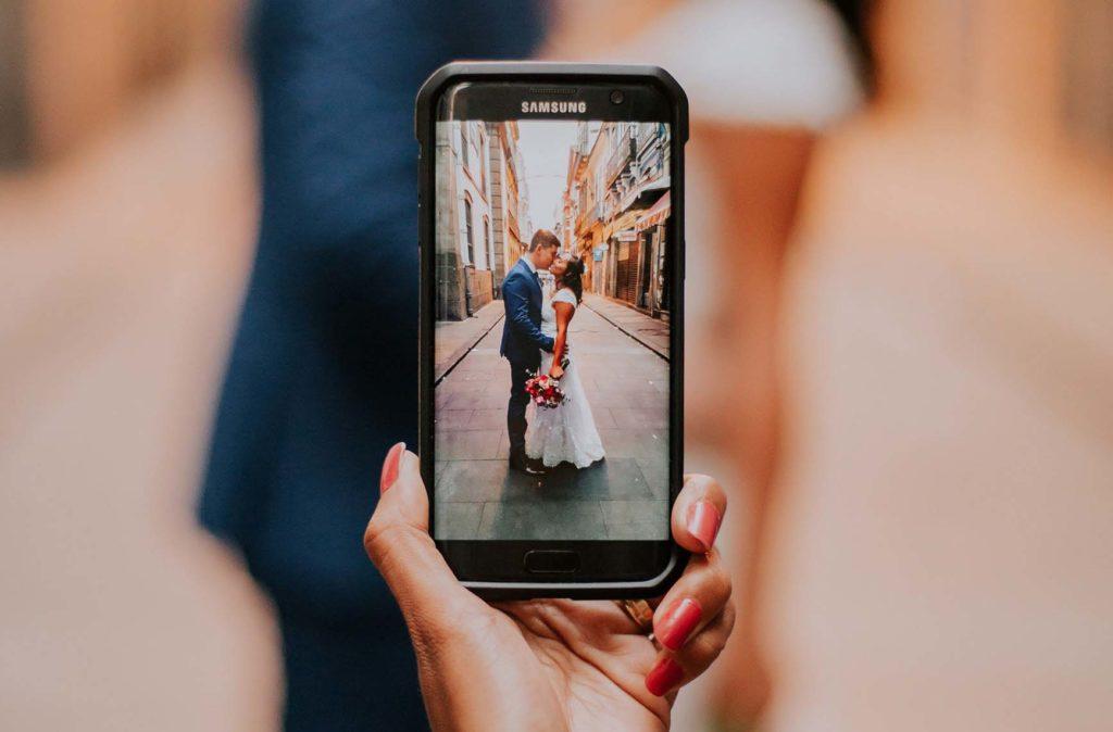 スマホで撮影するウェディングカップルの写真