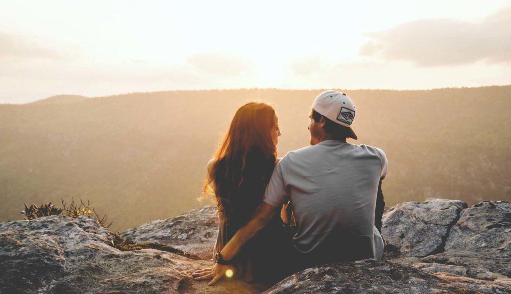 夕日の絶景の中、横に並んで座り見つめ合う男女カップルの写真