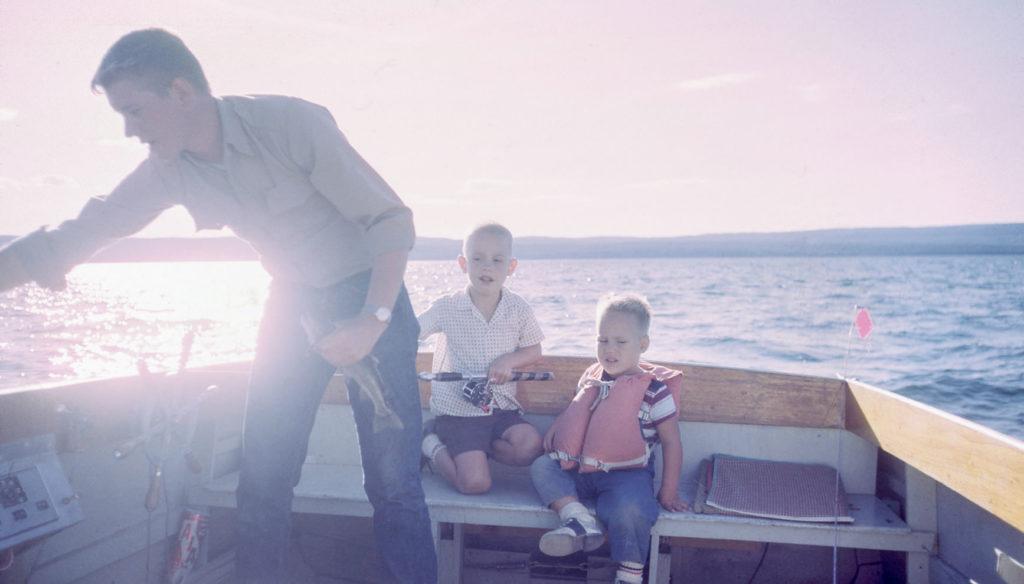 ボートに乗った2人の息子と父親の写真