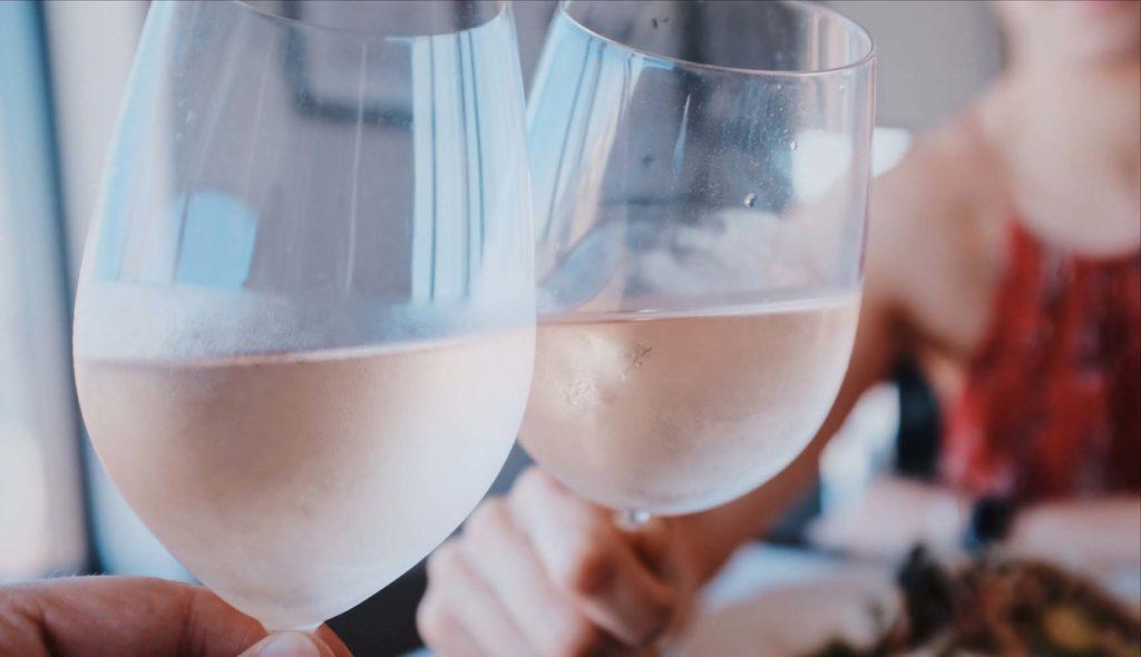 ワイングラスで乾杯するディナー中の男女の写真