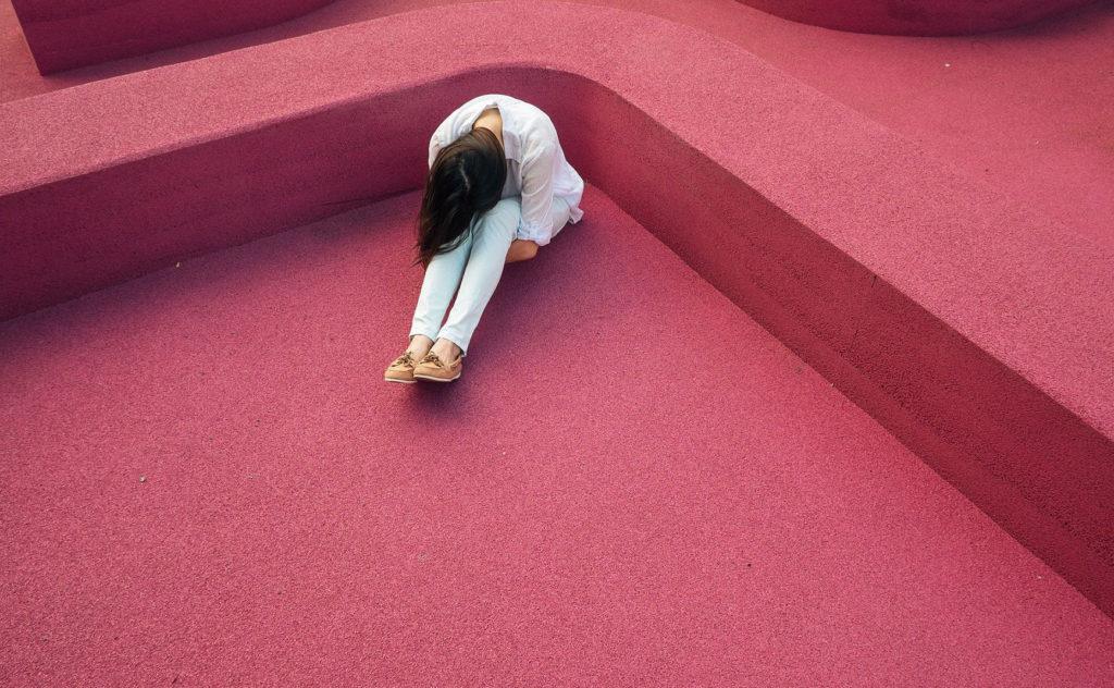 ピンク色の床に座り込み顔を伏せて落ち込んでいる女性の写真