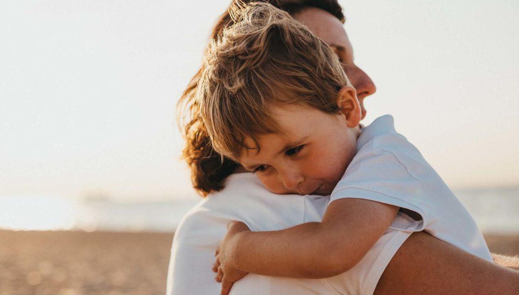 親に抱っこされながら神妙な面持ちの3歳くらいの男の子の写真