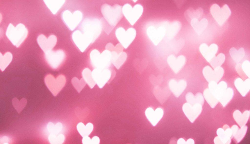 ピンクの背景に光るハートがたくさんの画像