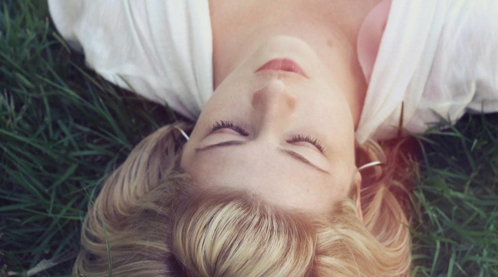 草原に横たわり目を閉じる女性の写真