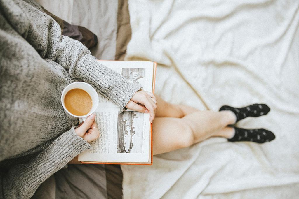 白いシーツのベッドの上で、本を開きコーヒーカップを手にしているが、飲むでも読むでもない様子の女性の写真