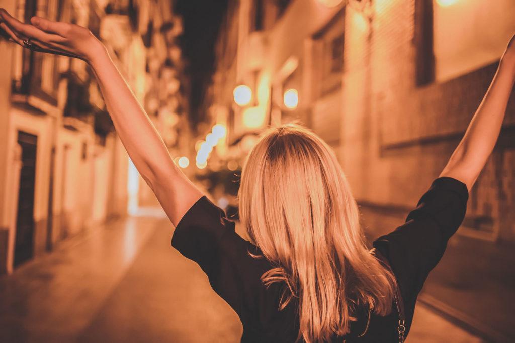 夜の街で楽しそうに両手を上げて歩いている女性の後ろ姿の写真