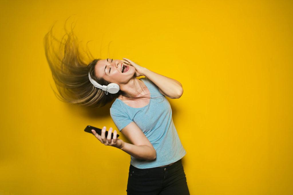 黄色の背景で、髪を振り乱して歌い喜ぶ女性の写真