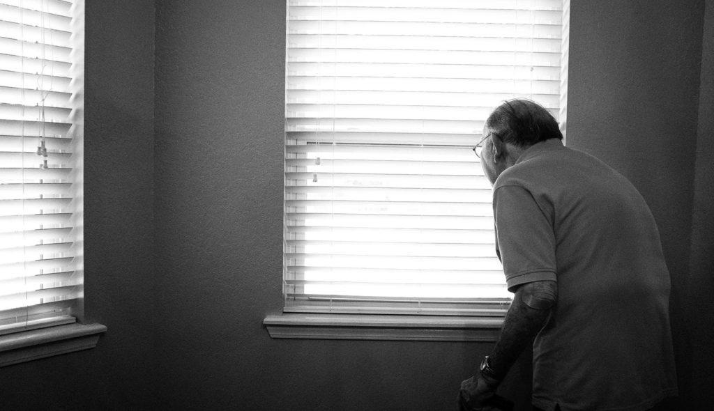 ブラインド越しに窓の外を見つめるおじいさんのモノクロ写真