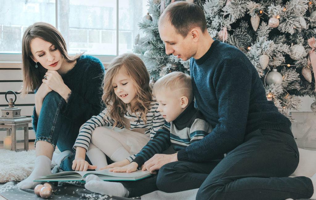 四人家族が絵本を見ている(母親は少し心の距離が遠く感じる)写真
