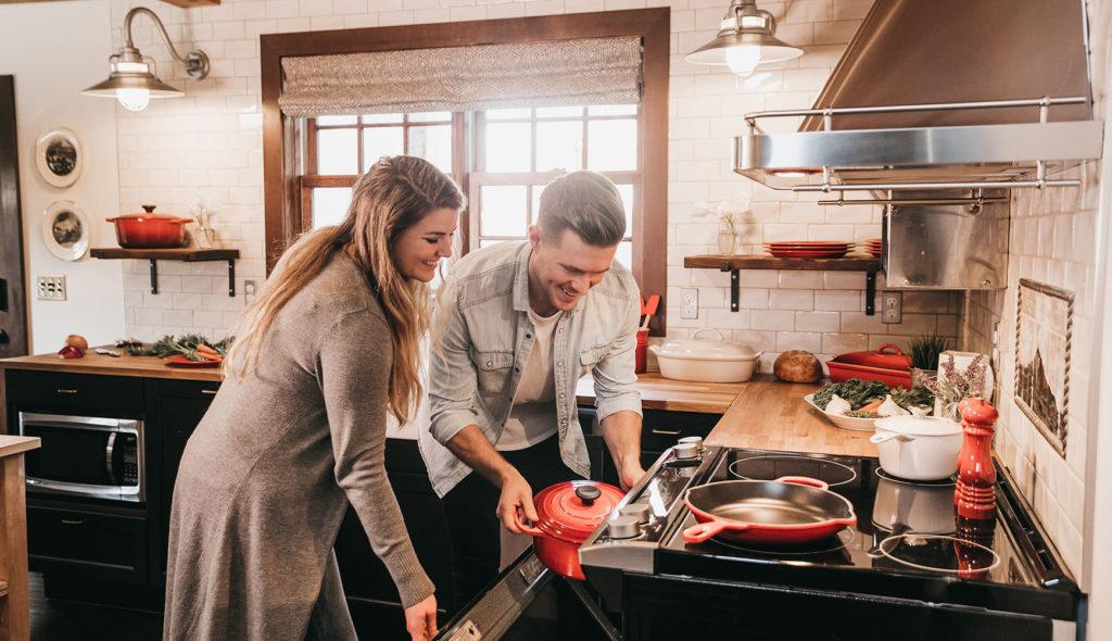 楽しそうな笑顔で、赤いル・クルーゼを手に持つ男性とオーブンのふたを開ける女性の写真