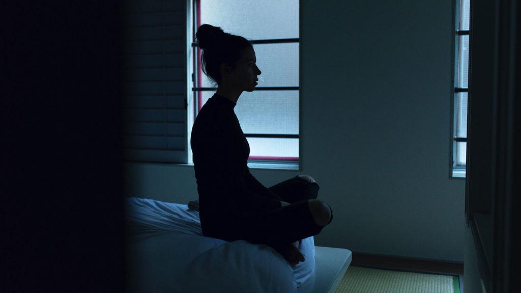 ぼーっとくうを見つめる女性が電気のついてない部屋で月明かりにシルエットが浮かぶ写真