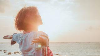 太陽の明るい光が溢れる海辺で両手を広げて大空を見つめている女性の後ろ姿の写真