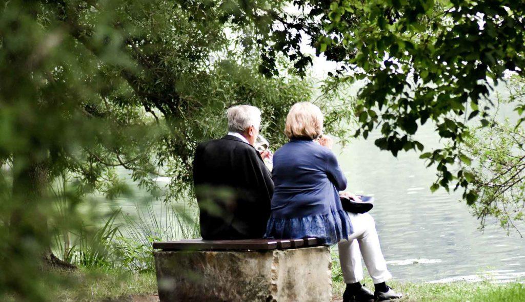 グリーンが綺麗な湖のほとりで二人並んで座っている老夫婦の後ろ姿の写真