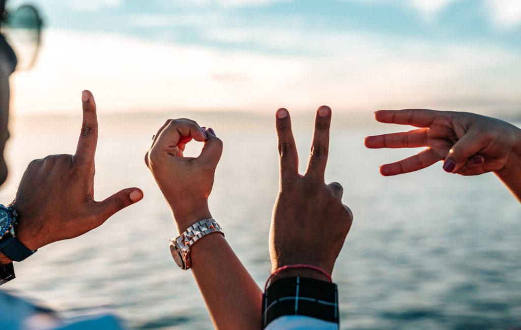 青い海と空を背景に、手でLOVEの文字を作っている写真