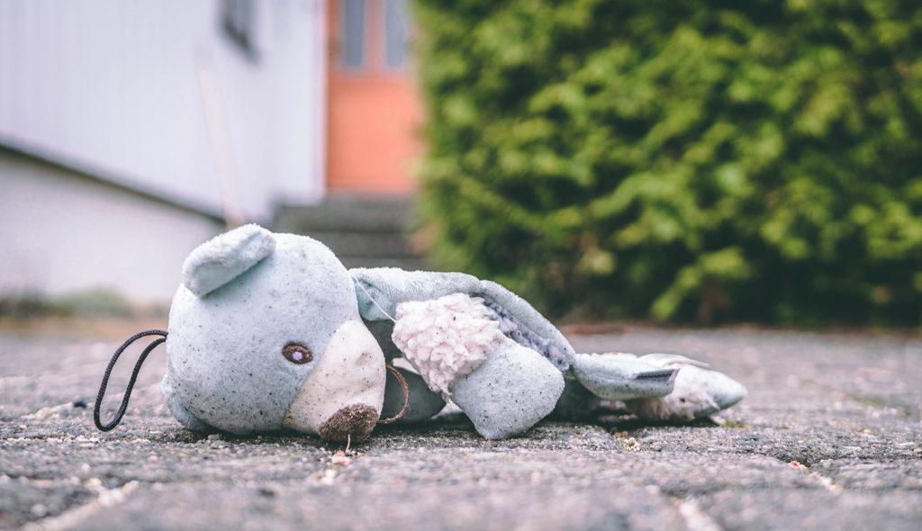 ボロボロになったクマのぬいぐるみが道に捨てられている写真
