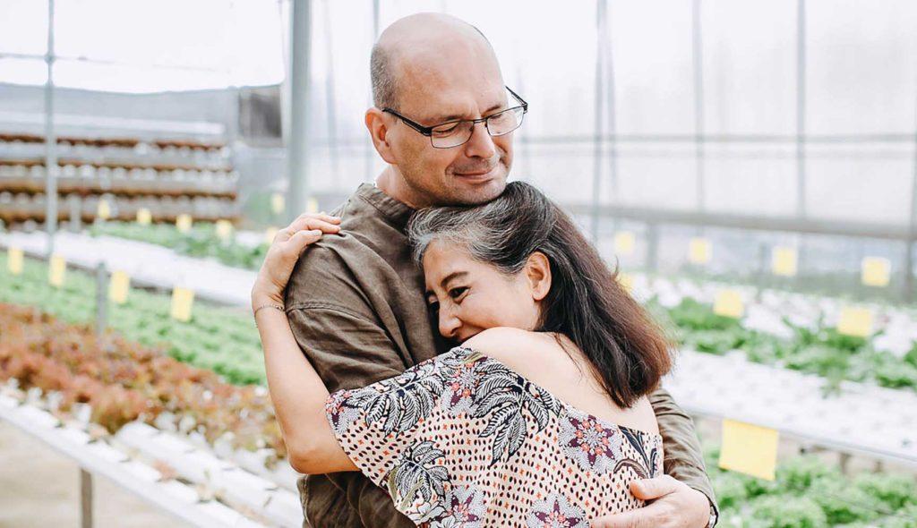 植物の並ぶ温室の中で幸せそうに抱き合う初老夫婦の写真