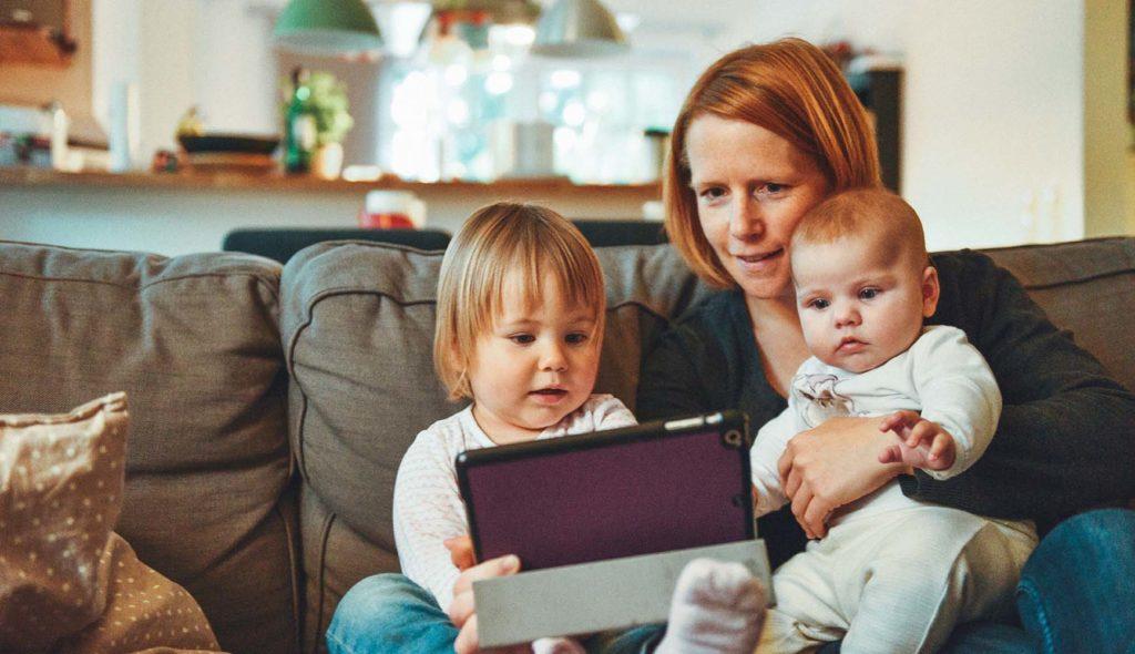 子供二人を抱えソファーに座ってタブレットをみている母親の写真