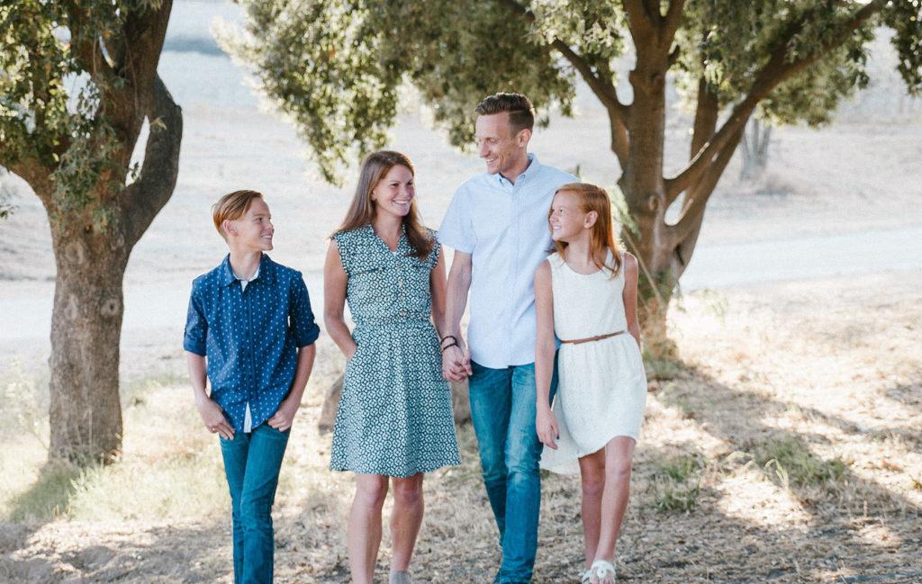 木陰の中を顔を見合わせながら歩く四人家族の写真