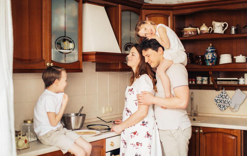 父親と子供二人がキッチンで料理している母親に寄り添っている写真