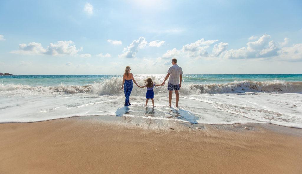 晴天の海を見つめ、5歳くらいの女の子を真ん中に三人で手を繋ぐ、ブルーのサマードレスがおしゃれな妻のいる家族の後ろ姿の写真