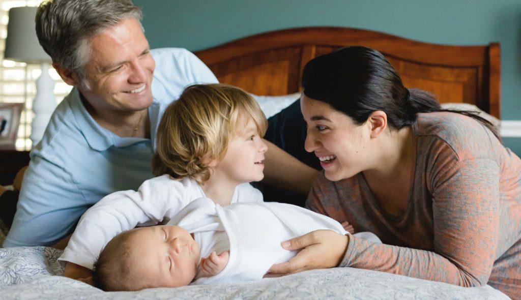 母親と6歳くらいの息子が顔を見合わせ、隣で父親も笑顔で見つめる、その息子の手元には生まれてたの赤ちゃんがいる、4人家族がベッドで団欒している写真