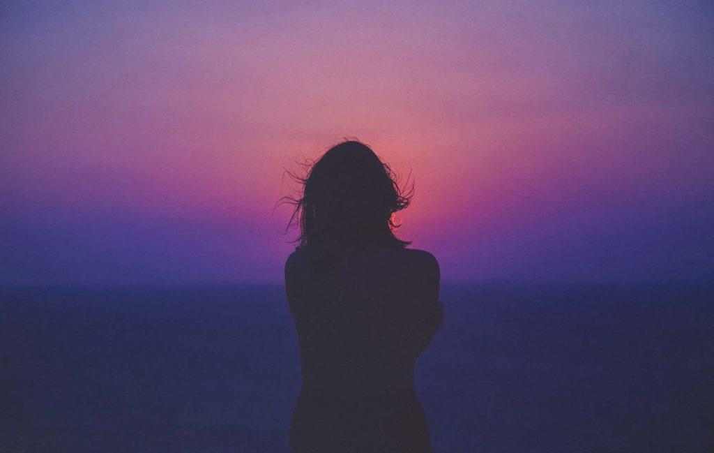 濃い紫からピンクのグラデーションの空と海を見つめている女性のシルエットの写真