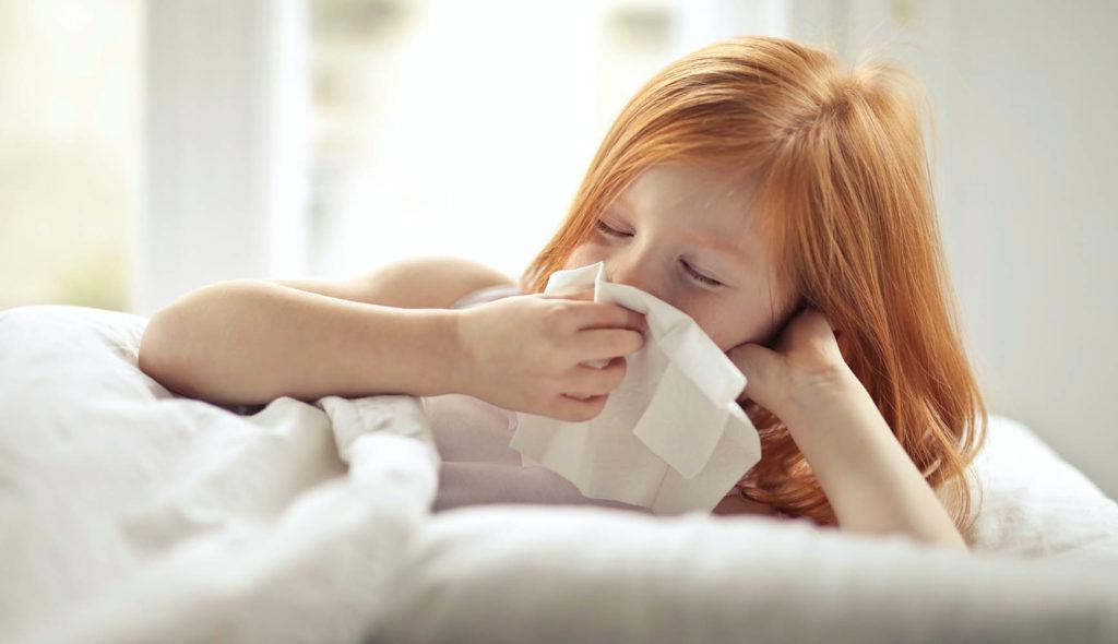 布団に入って鼻水かんでる10歳くらいの女の子の写真