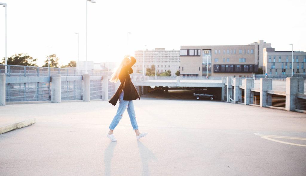朝日の中、都会を散歩する女性の写真