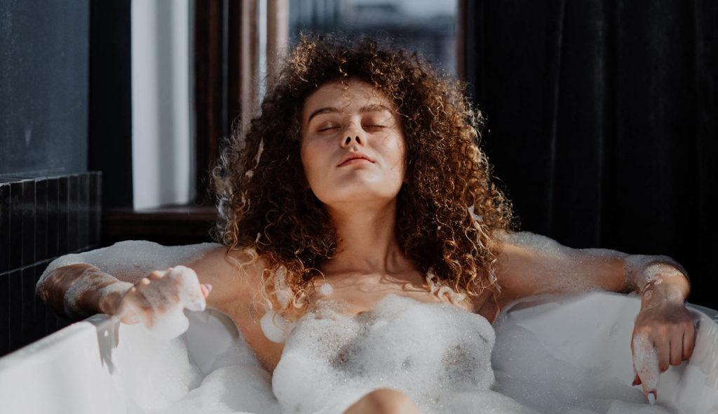 陽の光が差し込む泡風呂で目を瞑り気持ち良さそうに上を向いている女性の写真