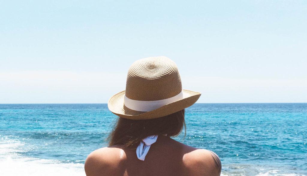 海を見つめる女性の後ろ姿の写真