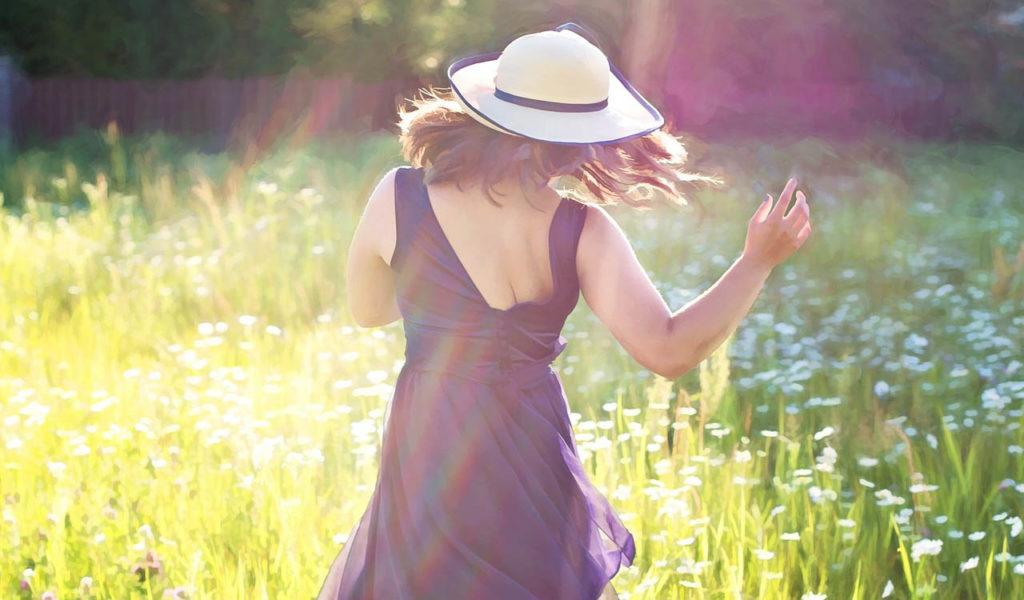 光の差す野原で楽しそうに踊る女性の後ろ姿の写真