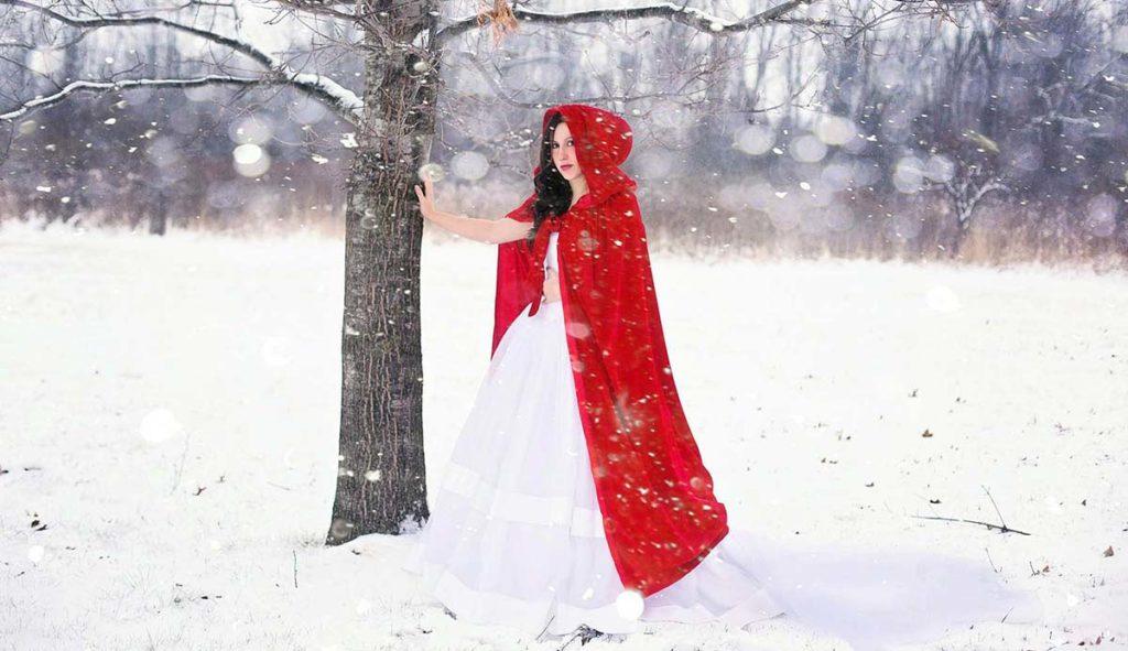 白雪姫のような赤いコートに白いドレスを着て雪の降る森に佇む女性の写真