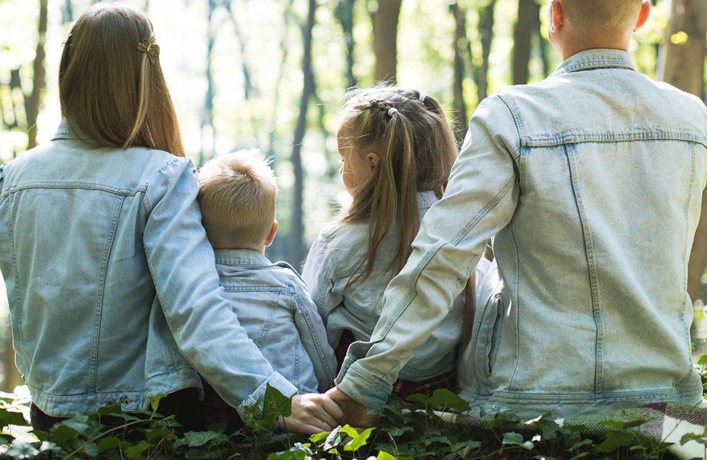 森の中で二人の子供を真ん中に挟み座る、お揃いのデニムを着た4人家族の後ろ姿写真。背中側で子供に気づかれないように手を握る夫婦の写真