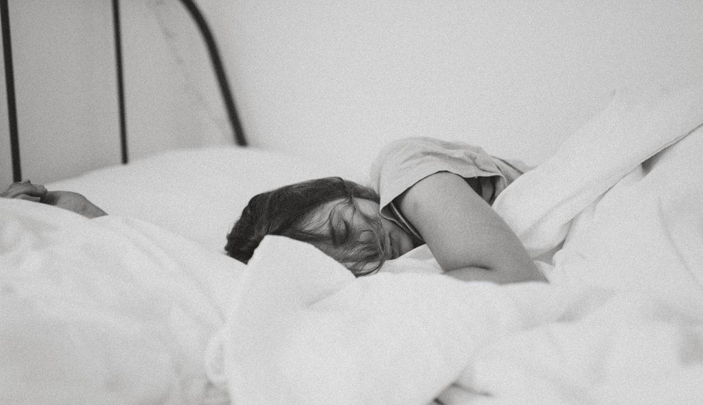 ベッドで横向きになり眠る女性のモノクロ写真
