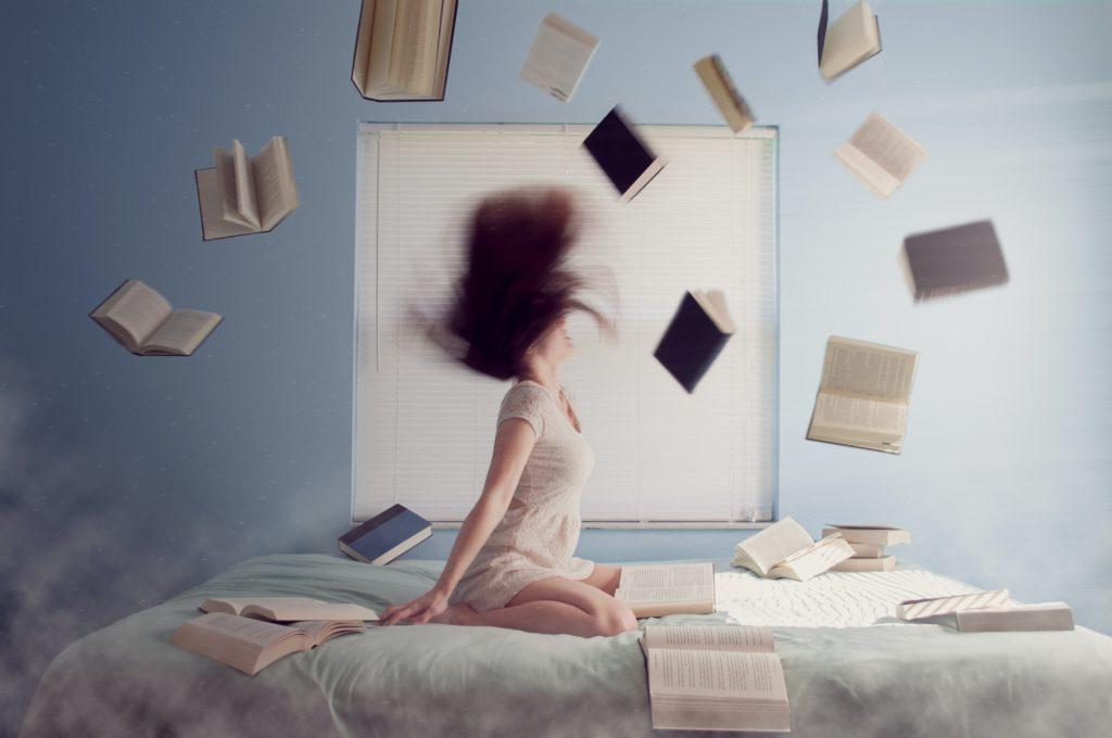 ベッドの上に座り髪の毛をブワッと振り上げる女性と、その周りに飛んでいるたくさんの本の写真