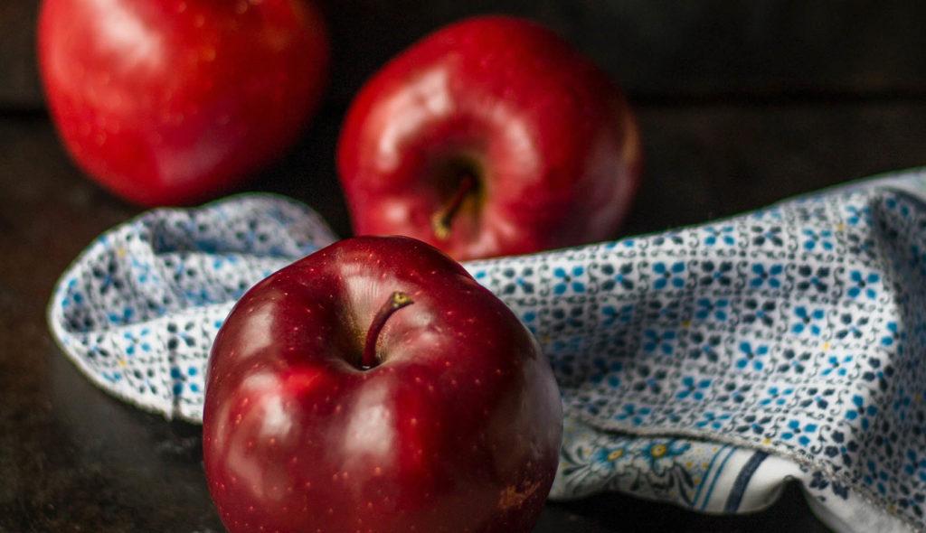 黒い背景にツヤツヤで真っ赤な林檎が青い柄の布の上から三つ転がっている写真
