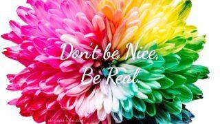 カラフルな色の花のアップショット写真。「Don't be Nice, Be real. 」の文字