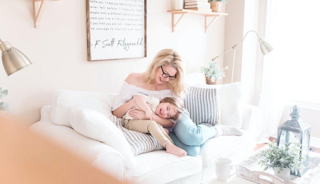 娘とソファの上で戯れる母親の、光に包まれた写真