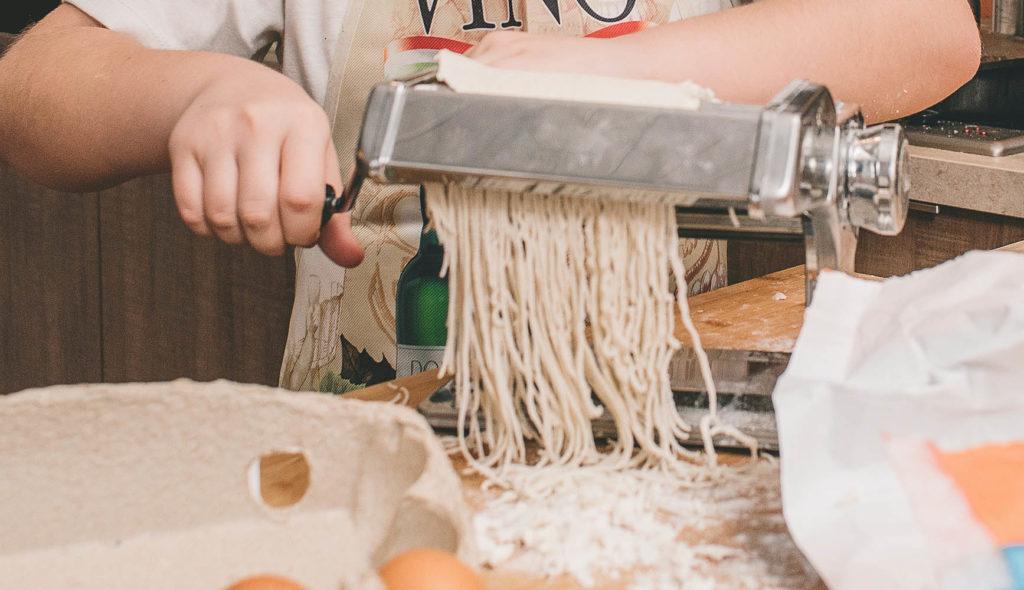 パスタを粉から練り機械に通して製麺している手元の写真