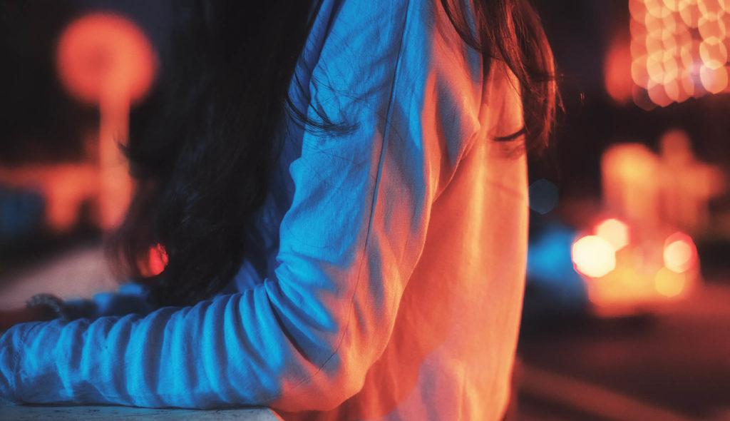 青とオレンジのライトが体に当たって二極化して見える、夜の陸橋で橋の向こうを見つめる女性の写真。